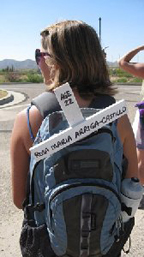 A young woman carrying a backpack with a white cross with words on it.