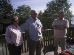 Three members of First Presbyterian Church of Craig and Klawock, talking together on a deck.