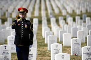 A lone U.S. Army bugler plays Taps at the conclusion of the First Annual Remembrance Ceremony in Dedication to Fallen Military Medical Personnel at Arlington National Cemetery.