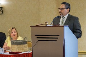 Tony De La Rosa, interim executive director of the Presbyterian Mission Agency, addresses the PMA Board following the announcement of his appointment alongside PMAB Chair Marilyn Gamm (seated.)