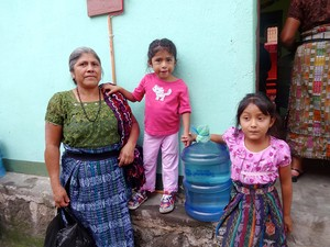 Guatemalan family receiving their first bottle of safe water from a new Living Waters for the World system.