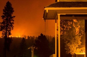 Flames on the hillside pictured with Nekisa Fellowship Hall of the First Presbyterian Church in Kamiah, Idaho, on the right.