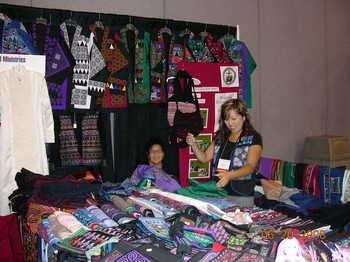 Chua Lee and her daughter arrange goods at their booth in the Global Marketplace. Their group, Fresno Interdenominational Refugee Ministries makes available Hmong cross stitch, reverse applique stitchery and other Southeast Asian refugee crafts.