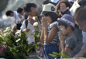 People praying on August 6, 2015, at a memorial in Hiroshima, Japan.