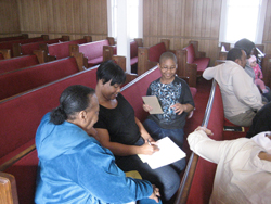 A small group of family members together, sitting in church pews.