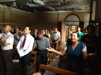 Members of Mallaway Presbyterian Church in Egypt held worship in their partially burned church days after it was set on fire by Islamist radicals.