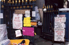 The exterior entrance of St. Paul's chapel, covered with signs, with packs of food near the entrance.