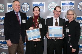 Ronald Drew (left), chair of the NYDIS board and Ruth Wenger (right),NYDIS executive vice-president present the NYDIS Partnership Award to Thia Reggio (second from left) on behalf of PDA and Robert Foltz-Morrison (second from right) of New York City Presbytery.