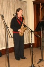 A woman in a church playing a saxophone.
