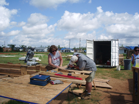 A group of volunteers working on a lumber at a site.