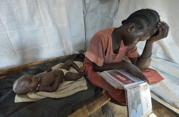 Nyanthem Mayol stares at photos of her relatives while her baby sleeps at her side in a temporary shelter near Ajoung Thok, South Sudan, where they fled after fighting broke out in their home town of Bentieu in late 2013.