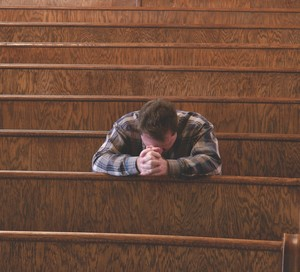 man praying in church pew
