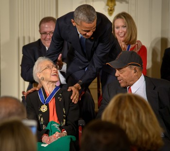 President Barack Obama presents former NASA mathematician Katherine Johnson with the Presidential Medal of Freedom, as professional baseball player Willie Mays, right, looks on, Tuesday, Nov. 24, 2015.