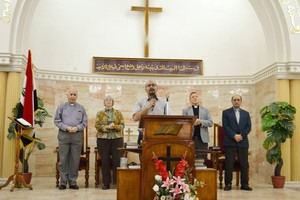 Elmarie and Scott Parker (left and right of podium) and Amgad Beblawi (far right) worship together in Bagdad.