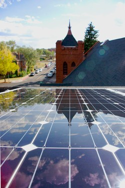 View of solar panels on top of Flagstaff Federated's gathering hall, overlooking the church's bell tower.