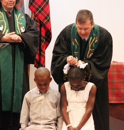 The Rev. John Odom, pastor of Starmount Presbyterian Church baptizes Marceline Kilassa and Benjamin Kibfoulwa, with teaching elder Kathryn Campbell, associate pastor (left). Both children received help through Black Child Development Institute.