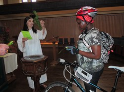 Using a sprig of cedar, officiant Ann Russell sprinkles holy water on a bike and its rider at the sixth annual Blessing of the Bikes at Toronto's Trinity-St. Paul's United Church on June 7, 2015.