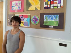 Chris Omelchuk standing in front of art he created at Beacon's after-school program.