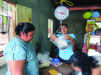 "Rosario Munoz purchases basic items from Nueva Vida's ""Pacifico Grocery Store,"" through which Pacific Presbytery is addressing root causes of poverty in Nicaragua."
